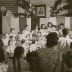 81  School choir singing, Judith Kibel playing piano. Trujillo portrait in background