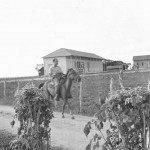 Settler on horse - barracks in background